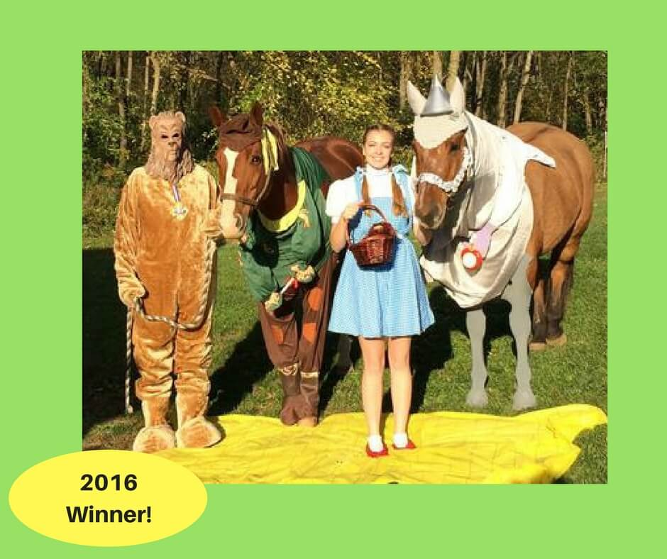 Two people dressed up as Dorothy and the lion from the movie the Wizard of Oz standing with two horses dressed up as the tin man and scarecrow from the same movie.