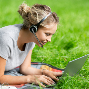 Girl looking at her computer with a headset on.