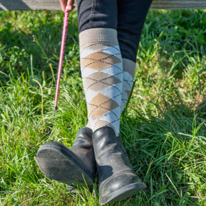 A pair of feet with boots and socks on with the socks showing.