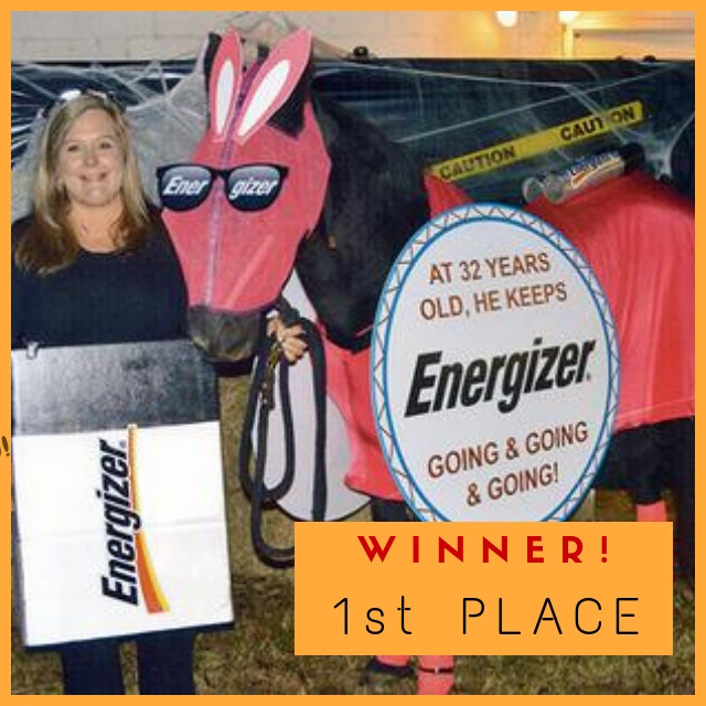 A horse dressed up as the Energizer bunny being held by a woman wearing a costume that makes her look like and Energizer battery.