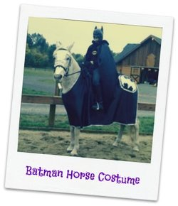 A horse dressed up as Batman being ridden by someone in a Batman costume.