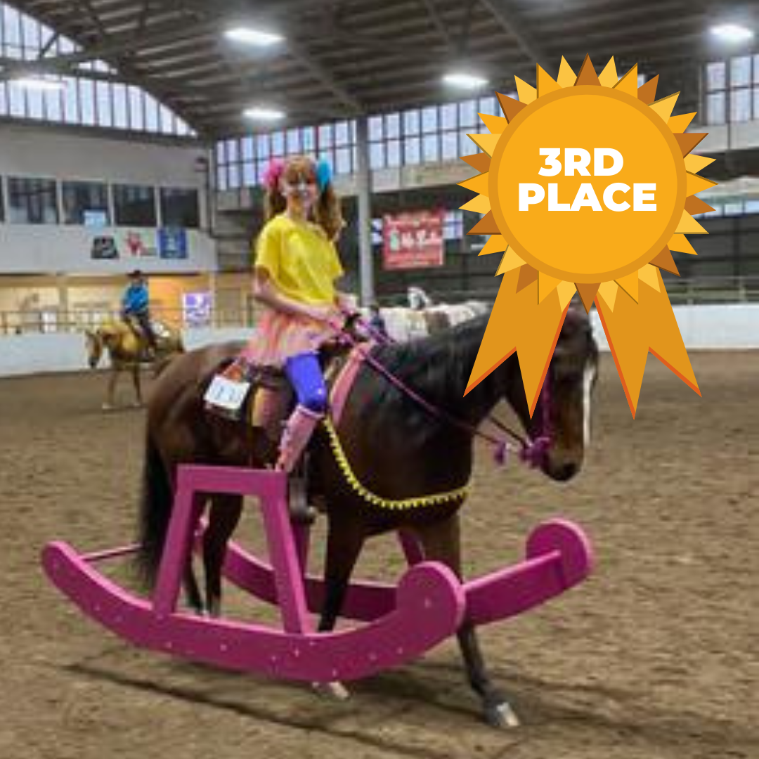 A horse dressed up to look like a rocking horse being ridden by a girl in a yellow shirt and a tutu to make her look like a little girl.